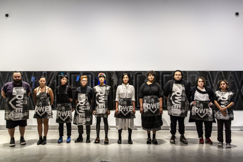 Installation view, Kay Abude, POWER 2018, participants in hand-printed silkscreen on linen garments in front of work by Janenne Eaton in National Anthem, Buxton Contemporary, the University of Melbourne, 2019, © the artists.⁣ Photograph by Bryony Jackson
